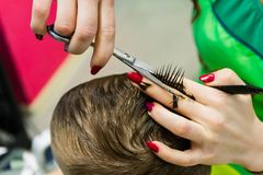 The hairdresser cuts the child. Haircut close-up. stock photo