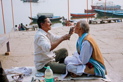 Hairdresser cuts client mustache on the banks of the river Ganges Stock Image