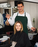 Hairdresser cuts hair of blonde girl at hairdressing saloon Royalty Free Stock Photos
