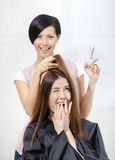 Hairdresser cuts hair of girl in hairdresser's Royalty Free Stock Image