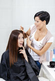 Hairdresser cuts hair of woman in hairdressing salon Royalty Free Stock Photo