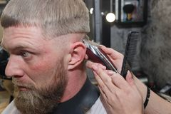 Hairdresser cuts machine man closeup in a barbershop stock photos