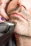 Hairdresser, cutting beard in her work place. Hairdresser, cutting beard of his customer with scissors and shave in the salon Royalty Free Stock Images