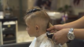 Hairdresser cutting children hair to little boy with electrical shaver in barber salon. Kids haircut with hair machine. Close up. Barber doing kid hairstyle in stock video footage
