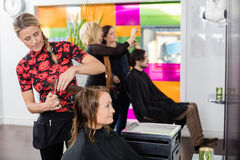Hairdresser Cutting Client's Hair In Beauty Salon Royalty Free Stock Photography