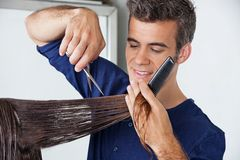 Hairdresser Cutting Client's Hair. Male hairdresser cutting client's wet hair in salon royalty free stock photography