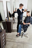 Hairdresser Cutting Client's Hair In Parlor Stock Images