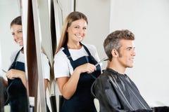 Hairdresser Cutting Client's Hair Stock Photos