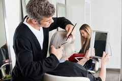 Hairdresser Cutting Client's Hair At Salon Royalty Free Stock Photo