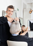 Hairdresser Cutting Client's Hair At Salon Royalty Free Stock Image