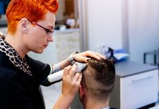 Hairdresser cutting customer hair with electric trimmer. Male in hairdresser salon stock photo