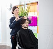 Hairdresser Cutting Customer's Hair In Salon stock images