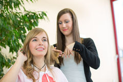 Hairdresser cutting customers hair in salon Stock Images