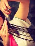 Hairdresser cutting dark hair using professional scissors Stock Images