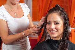 Hairdresser cutting hair of the beautiful smiling girl Stock Photos