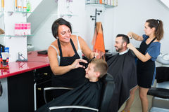 Hairdresser cutting hair of boy Royalty Free Stock Photo
