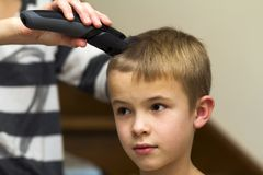 Hairdresser is cutting hair of a child boy in barber shop.  royalty free stock photo