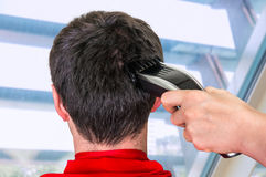 Hairdresser cutting hair with electric hair clipper in barber sh. Hairdresser cutting black hair with electric hair clipper in barber shop stock photos