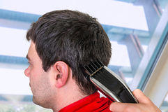 Hairdresser cutting hair with electric hair clipper in barber sh. Hairdresser cutting black hair with electric hair clipper in barber shop stock photo