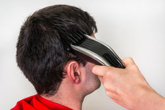 Hairdresser cutting hair with electric hair clipper in barber sh. Hairdresser cutting black hair with electric hair clipper in barber shop stock images