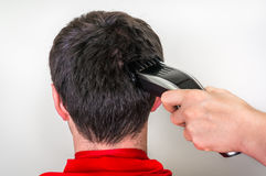 Hairdresser cutting hair with electric hair clipper in barber sh. Hairdresser cutting black hair with electric hair clipper in barber shop royalty free stock photos