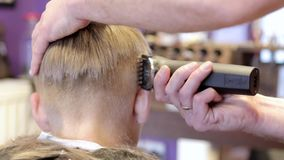 Hairdresser cutting hair by electric trimmer stock video