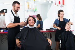 Hairdresser cutting hair of female client Royalty Free Stock Photo