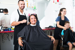 Hairdresser cutting hair of female client Royalty Free Stock Photos