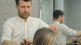 Hairdresser cutting hair in salon closeup stock footage