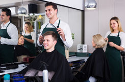 Hairdresser cutting hair of teenage Stock Image