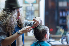 Hairdresser cutting kid hair Royalty Free Stock Images