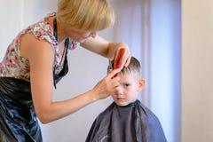 Hairdresser cutting a little boys hair Stock Photography