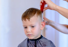 Hairdresser cutting a little boys hair Royalty Free Stock Images