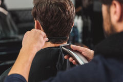 Hairdresser cutting male hair by machine. Professional barber is doing hairstyle by shearer and comb Royalty Free Stock Photography