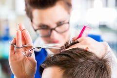 Hairdresser cutting man hair in barbershop Royalty Free Stock Image