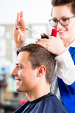 Hairdresser cutting man hair in barbershop Royalty Free Stock Photography