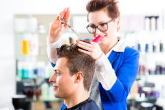 Hairdresser cutting man hair in barbershop. Female coiffeur cutting men hair in hairdresser shop stock photography