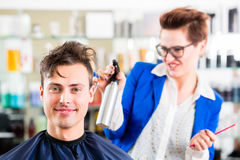 Hairdresser cutting man hair in barbershop. Female coiffeur cutting men hair in hairdresser shop royalty free stock images