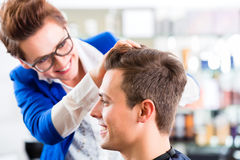 Hairdresser cutting man hair in barbershop. Female coiffeur cutting men hair in hairdresser shop royalty free stock photography