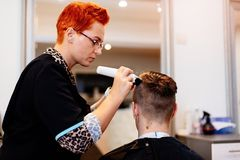 Hairdresser cutting man`s hair with electric trimmer. Woman hairdresser cutting man`s hair with electric trimmer stock photography