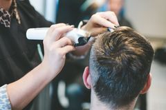 Hairdresser cutting man`s hair with electric trimmer. Woman hairdresser cutting man`s hair with electric trimmer royalty free stock photography