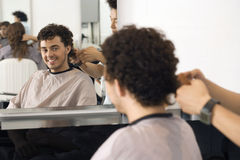 Hairdresser cutting man's hair in salon, reflection in mirror, smiling, rear view, portrait Stock Photography