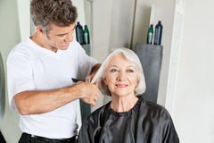 Hairdresser Cutting Senior Client's Hair Stock Photo