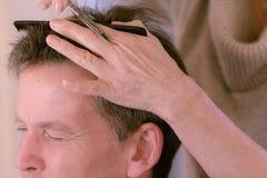 Hairdresser cutting senior man's hair royalty free stock image