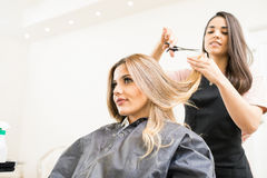 Hairdresser cutting some hair tips. Pretty brunette working as a hairdresser and cutting hair tips of a female customer in a beauty salon Stock Photo
