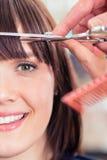 Hairdresser cutting woman bangs hair Royalty Free Stock Images