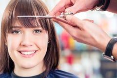 Hairdresser cutting woman bangs hair. Hairdresser cutting women bangs hair in shop royalty free stock photo