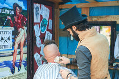 Hairdresser in the cylinder cap. CHERNIVTSI, UKRAINE - JULY 22, 2017: Stylish hairdresser in the cylinder cap Shears and shaves a biker with red hair at the Royalty Free Stock Photo