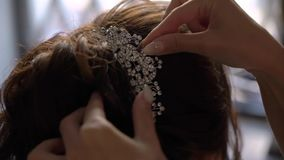 The hairdresser does the bride`s hair. Wedding hairstyle for a young girl. Stylist doing hair styling