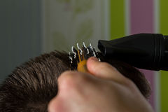 Hairdresser does hair with brush and hairdryer of client in professional hairdressing salon stock image